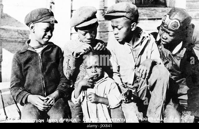 Four young African American boys sit outside and look at the top of a young African American girl's head as - Stock Image