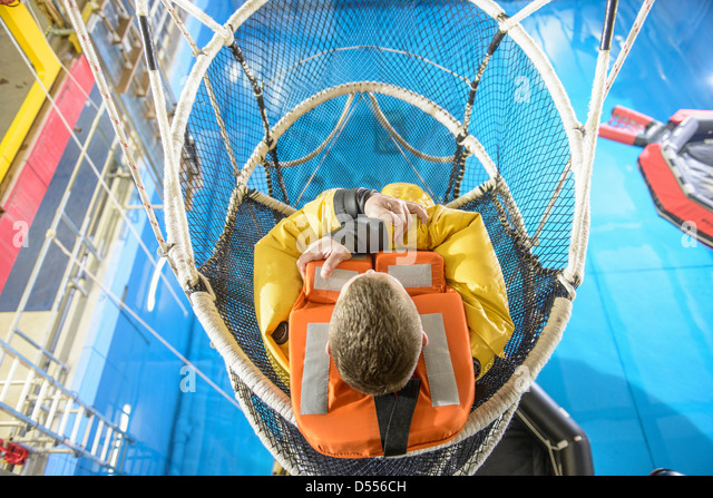 Oil worker training in escape net - Stock Image