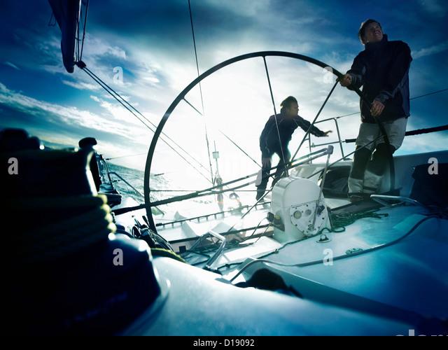 Sailors steering yacht - Stock Image