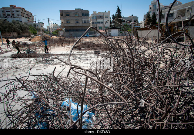 Youths reclaiming metal from bomb damage to be used again in construction in Gaza City, Gaza, Palestinian Territories. - Stock Image