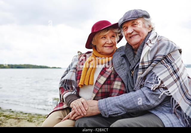Retired seniors having rest by seaside in autumn - Stock Image