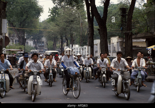 Vietnam Saigon Ho Chi Minh City residents traffic motor scooters bicycles - Stock Image