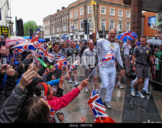 Runner 071 Brings the olympic flame into Warrington up Sankey St, near Golden Square shopping area - Stock Image