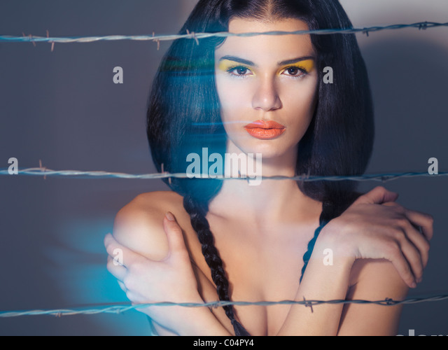 Artistic expressive beauty portrait of a young beautiful woman behind barbed wire - Stock Image