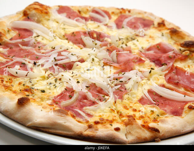 Delicious fresh pizza with ham and onions on white background. Selective focus, shallow DOF - Stock Image