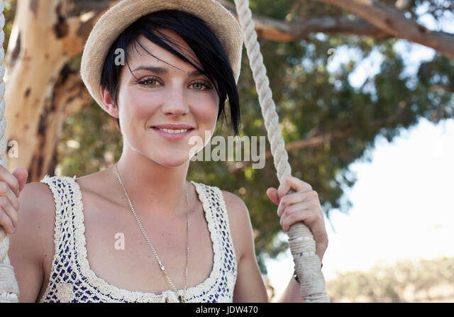 Young woman sitting on swing - Stock-Bilder