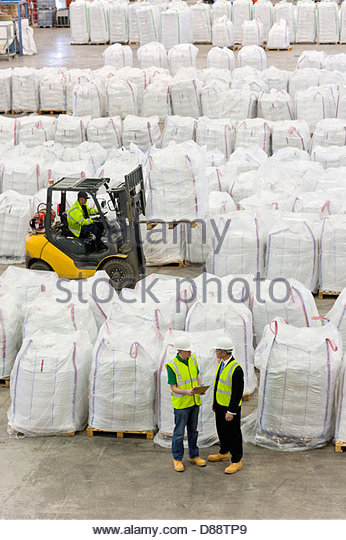 Businessman and workers among large bags of recycled plastic pellets in warehouse - Stock Image