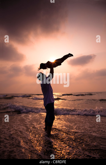 the silhouette of happy family on the beach - Stock Image