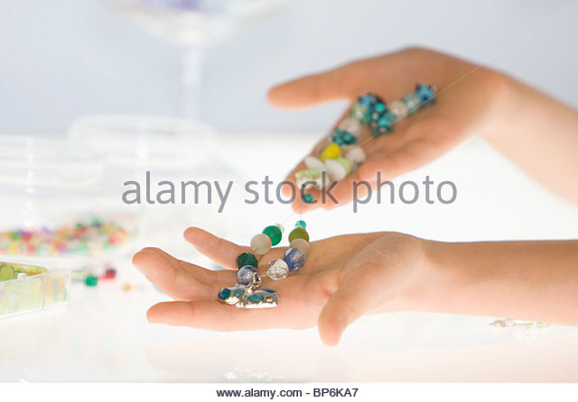 A young girl holding a bead necklace, close-up of hands - Stock Image