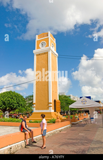 Cozumel Mexico San Miguel town Parque Benito Juarez La Plaza  bright yellow clock tower - Stock Image