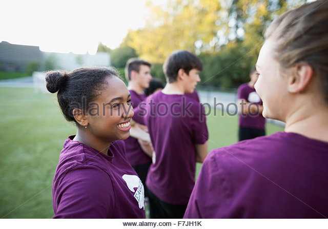 Smiling high school students talking in physical education - Stock Image