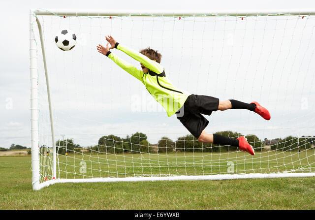 Boy goalkeeper jumping to save goal - Stock-Bilder