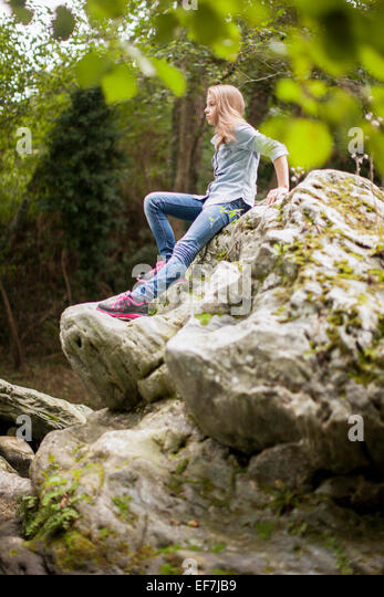Girl sitting on rock in a park - Stock Image