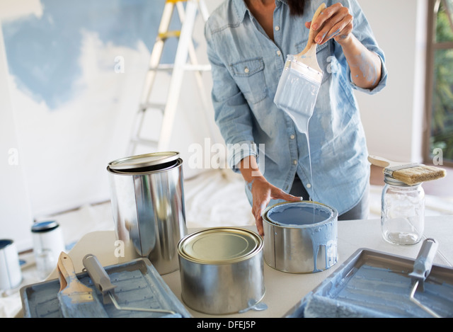 Woman holding paintbrush with blue paint - Stock Image