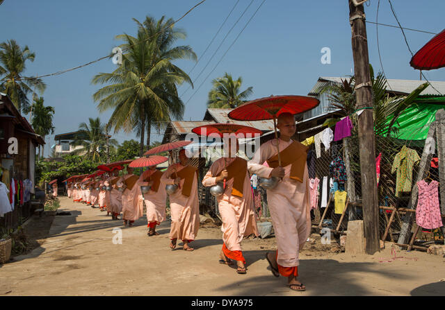 Kyauktan Myanmar Burma Asia Parade Yangon Rangoon aligned colourful culture donation nuns parading pink red religion - Stock Image