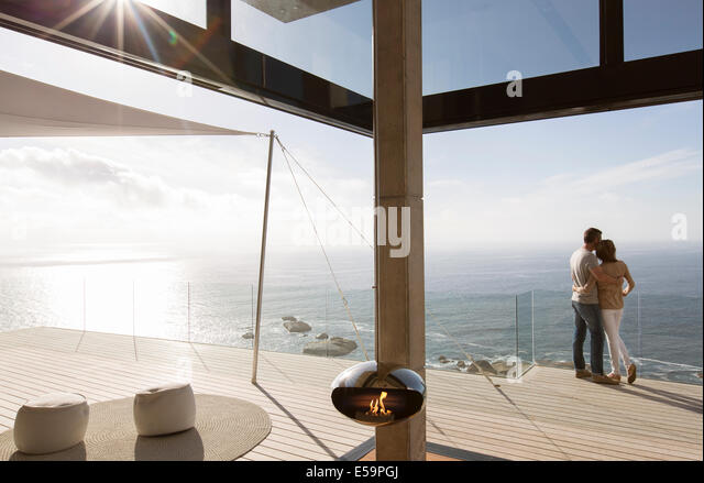 Couple standing on balcony of modern home - Stock Image