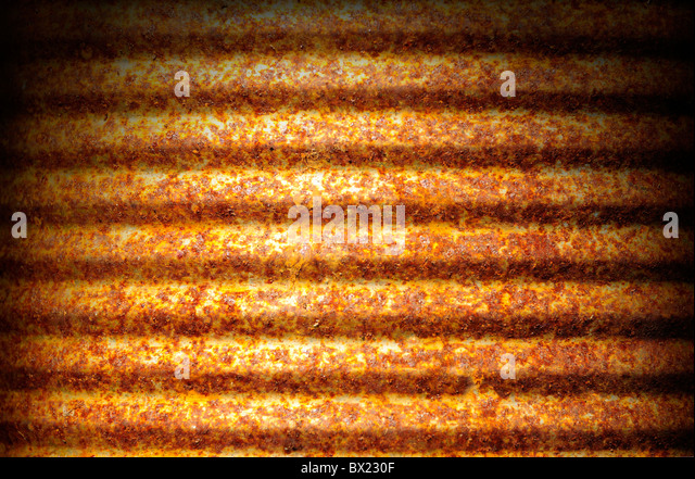 Rusty corrugated metal can surface lit dramatically from above - Stock Image
