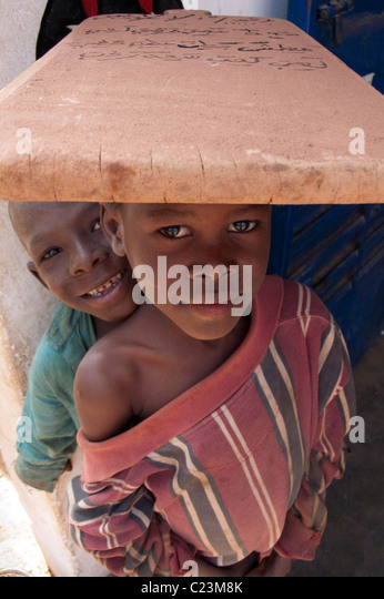Schoolboy carrying writing tablet on his head in the Kibédoué quarter of Bobo Dioulasso - Stock Image