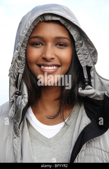 Woman smiling wearing warm hooded jacket - Stock Image