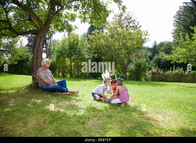 Tied up grandfather with grandchildren - Stock Image