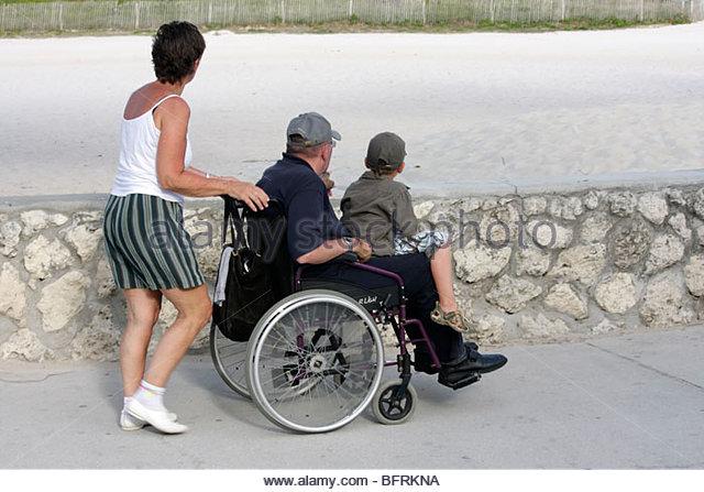 Miami Beach Florida Lummus Park walkway coral rock wall woman man boy family wheelchair push disabled - Stock Image