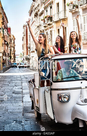 Three young women waving from open back seat of Italian taxi, Cagliari, Sardinia, Italy - Stock Image
