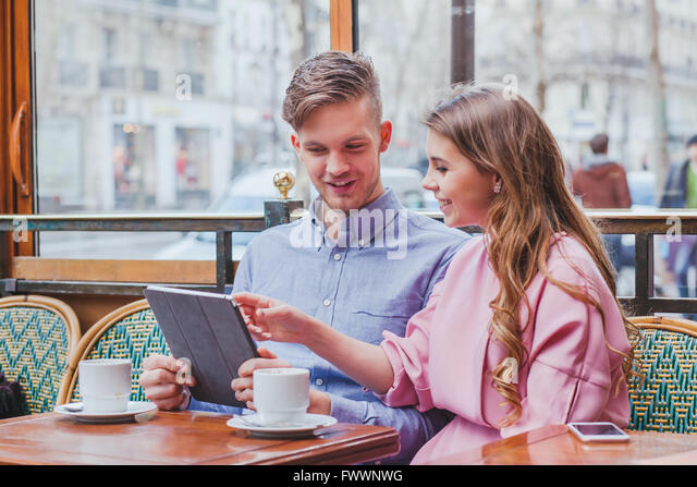 young couple with digital tablet in cafe, smiling happy man and woman looking to the screen, using internet, buy - Stock-Bilder