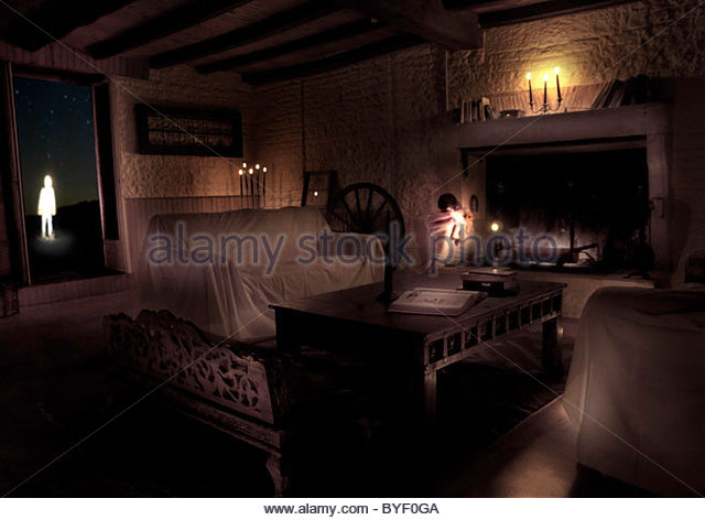 Dark empty room with covers over seats and small figure of child standing in doorway - Stock Image