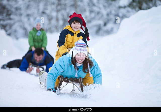 Germany, Bavaria, Family sledding, having fun - Stock Image