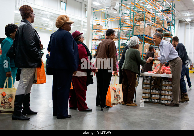 US President Barack Obama greets people during a family service project at the Capital Area Food Bank November 21, - Stock Image