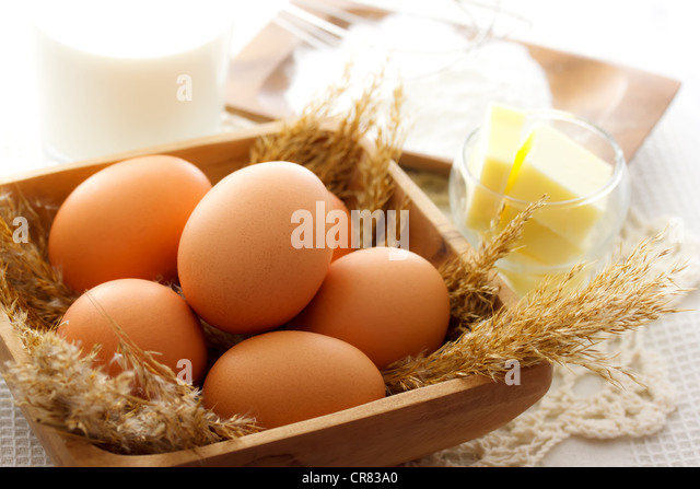 Fresh eggs with butter and flour (cake ingredients) - Stock Image