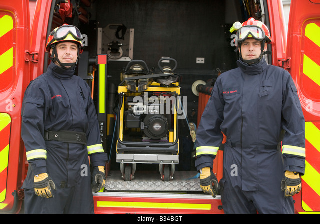 Two rescue workers standing by open back door of rescue vehicle - Stock Image