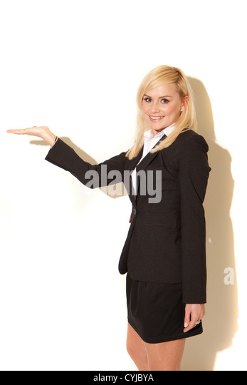 Smiling blonde professional saleswoman with her hand extended with an empty palm for your product placement and - Stock Image