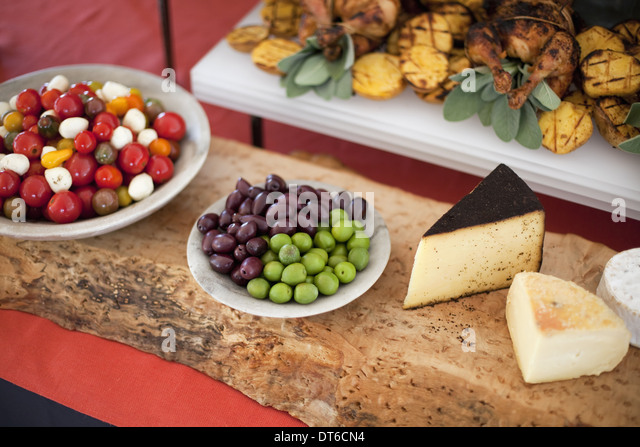 Organic food presented on white dish. Cheese, free range chicken, heritage tomatoes and salad ingredients. Farmstand - Stock Image