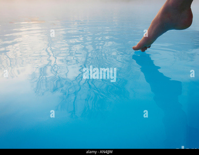 Toe feeling water temperature in outdoor swimming pool - Stock Image