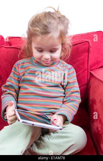 Adorable shy little girl with a tablet-pc in her hands sitting smiling with downcast eyes on a red sofa - Stock Image