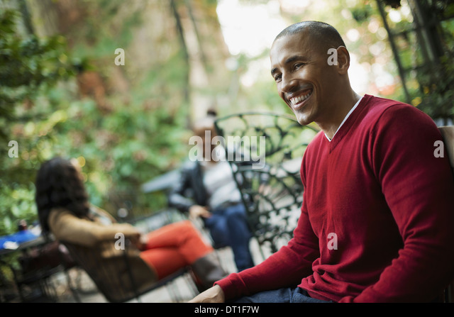 Scenes from urban life in New York City Three people sitting in an outdoor space Man woman and teenager - Stock Image