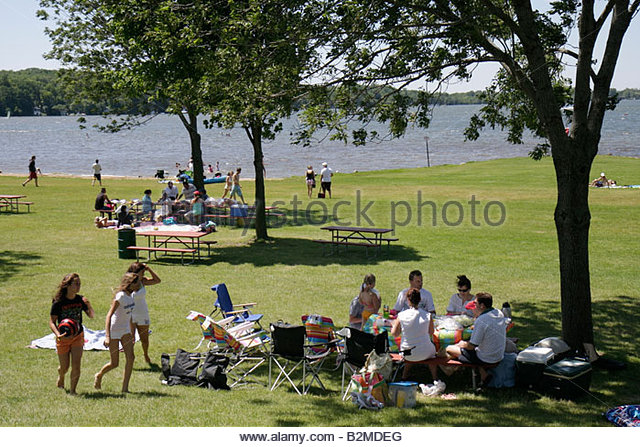 Wisconsin Kenosha Silver Lake Silver Lake Park picnic benches girls teen family outdoor fun summer vacation men - Stock Image