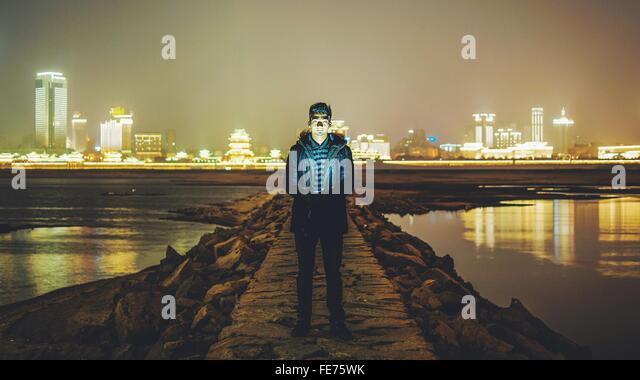 Portrait Of Young Man Standing On Pier Amidst River At Night - Stock Image