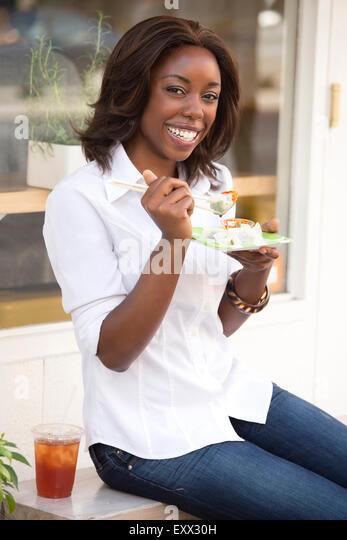 Smiling woman eating dumplings - Stock Image