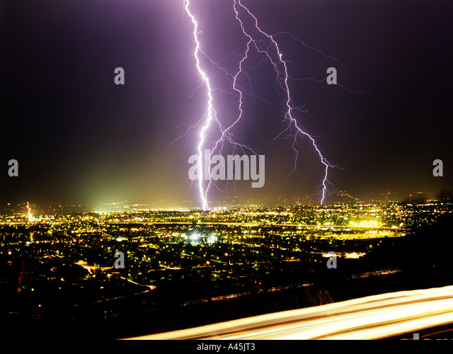 Lightning strikes from a black sky over a glowing cityscape in Southern Arizona, USA. - Stock Image
