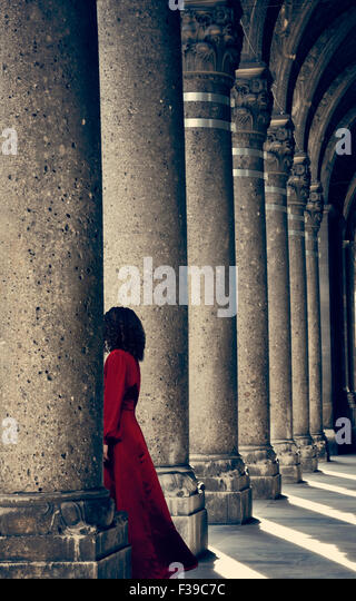 Mysterious woman in red dress behind column - Stock Image