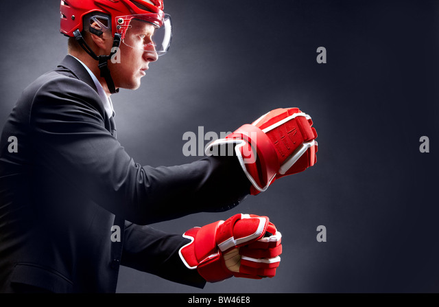 Portrait of young businessman in suit and hockey helmet and gloves fighting - Stock Image