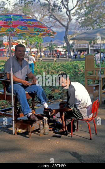 Isla Margarita island Venezuela Porlamar city man shining shoes in city park - Stock Image