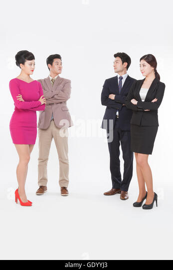 Contrasting business people in retro styles and black suits standing face to face with their arms folded - Stock Image