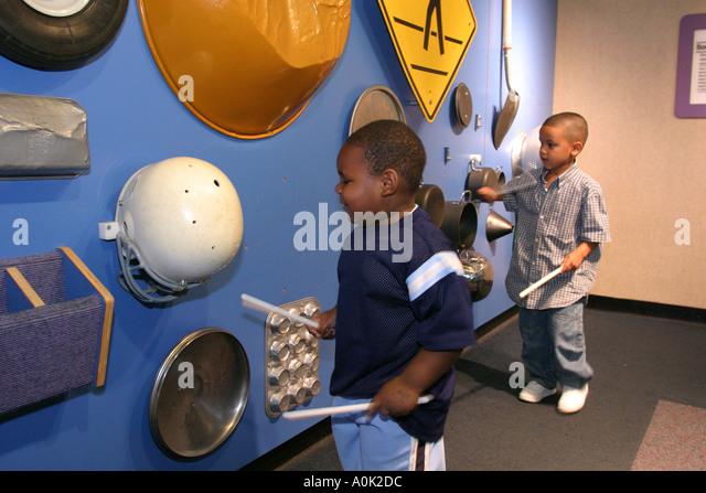 Toledo Ohio COSI Science Center drumming banging Black boys noise sounds - Stock Image