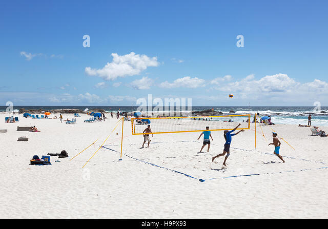 People playing beach volleyball on Camps Bay beach, Cape Town, South Africa - Stock Image
