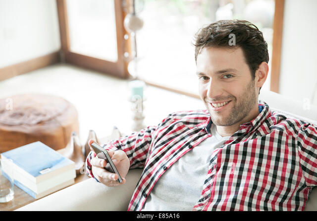 Man using smartphone at home, smiling - Stock-Bilder