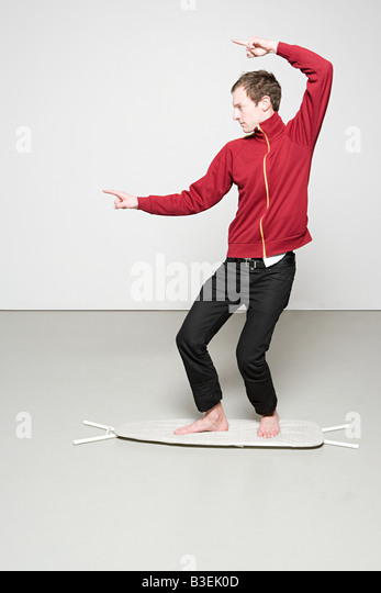 Man surfing on an ironing board - Stock Image