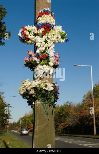 Roadside memorial to car crash victim. Cross of plastic flowers Weston Green Surrey Greater London  A307 - Stock Image